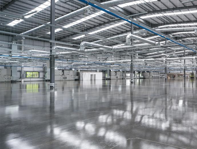 Im Bild ist eine moderne Industriehalle mit glänzendem grauen Boden zu sehen