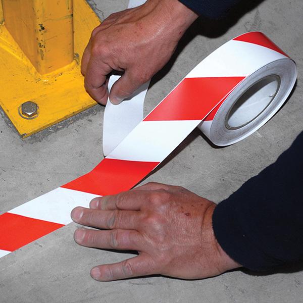 Im Bild: Ein rot weisses Markierungstape wird von Hand auf einem Betonboden aufgebracht