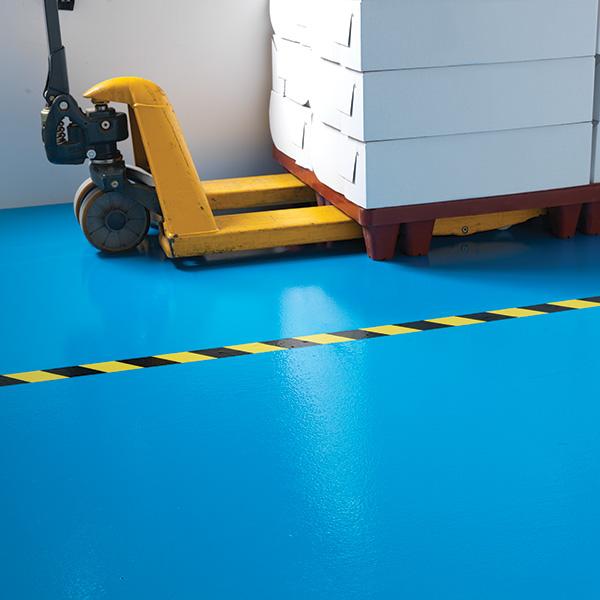 Im Bild ein Gabelstapler steht auf einem blau beschichtetem Boden mit einem gelb/schwarz gestreifen Markierungstape