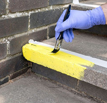 Im Bild wird eine Stufenkante mit gelber Farbe bepinselt