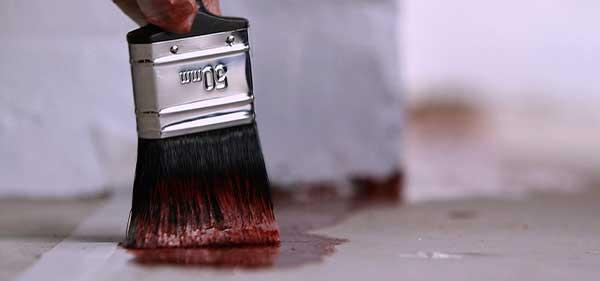Im Bild: Farbe wird mit einem Pinsel auf dem Boden aufgetragen