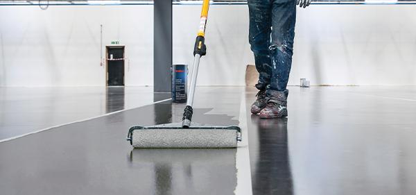 Im Bild: Eine Watco Beschichtung wir auf einem Industrieboden aufgetragen