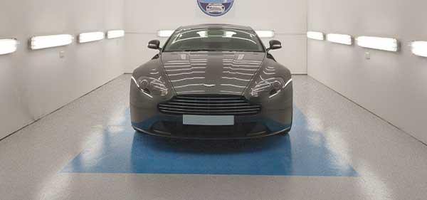 Bild eines Aston Martin in einem Showroom auf einer glänzenden Bodenbeschichtung. Klicken, um zu den Kundenprojekten zu gelangen.